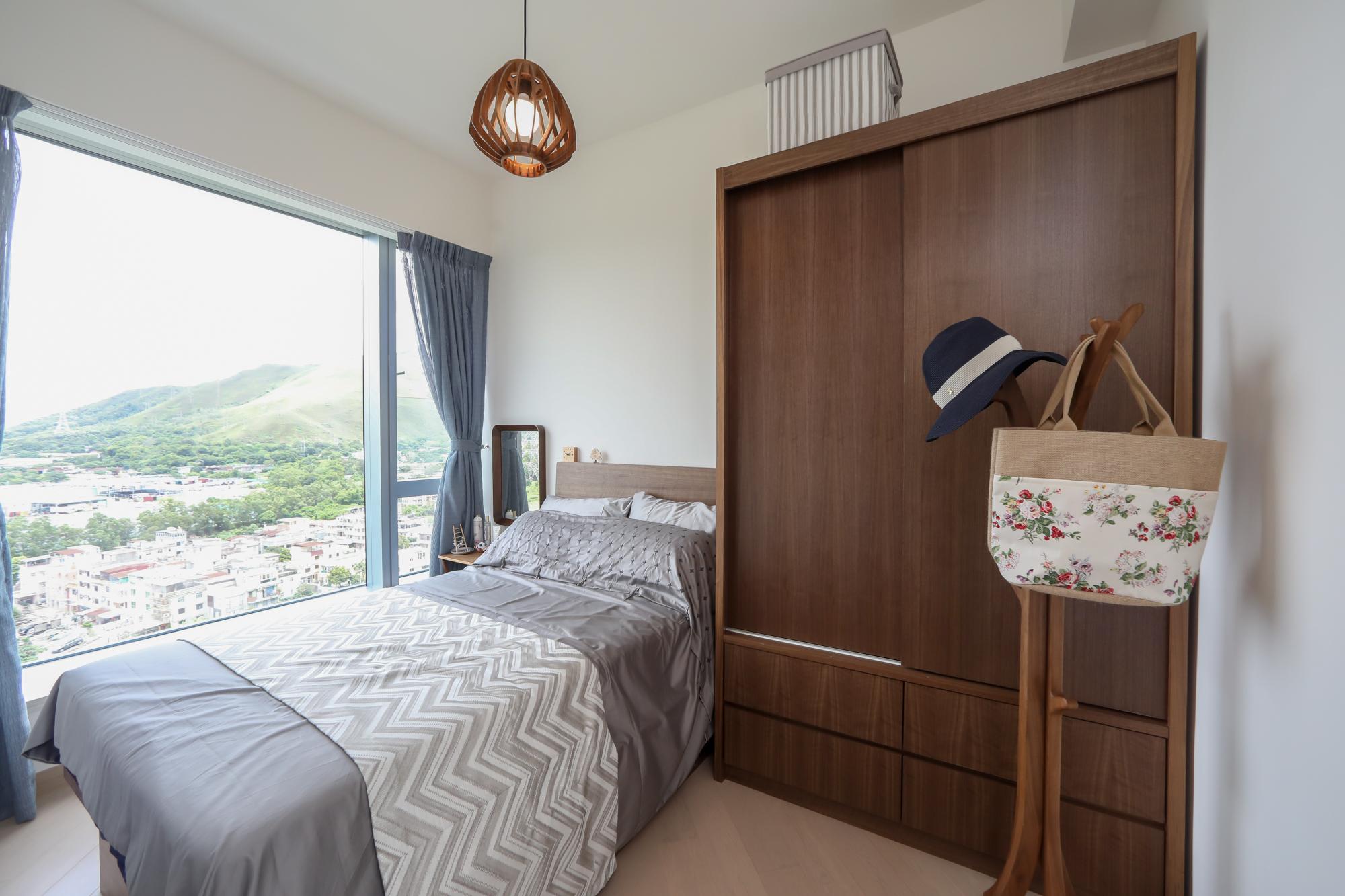主人睡房靠窗位置擺放一張雙人床配以灰銀色絲質被單,三邊落床的設計開揚大方。