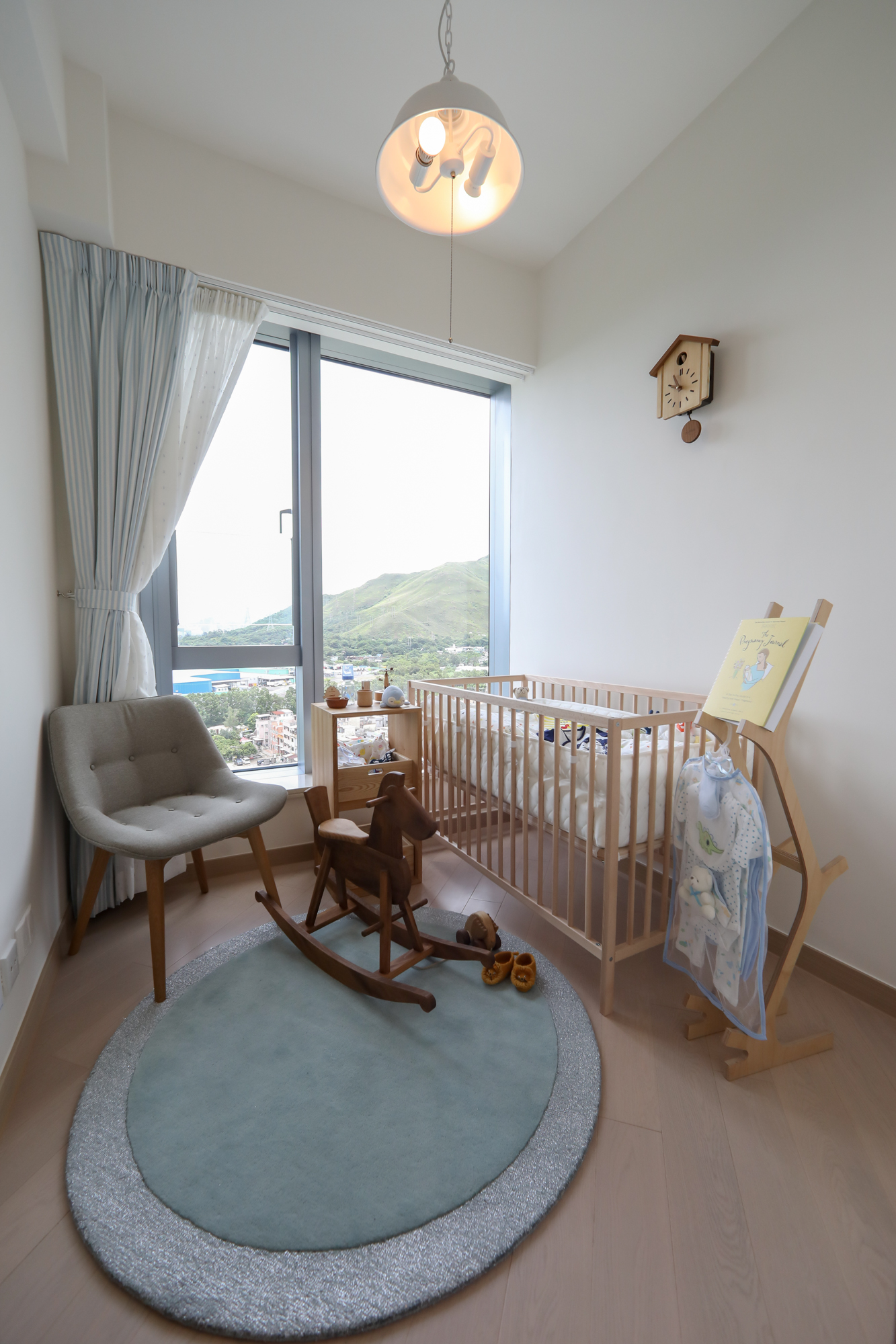 另一間睡房則放置淺色嬰兒床及木紋矮櫃。